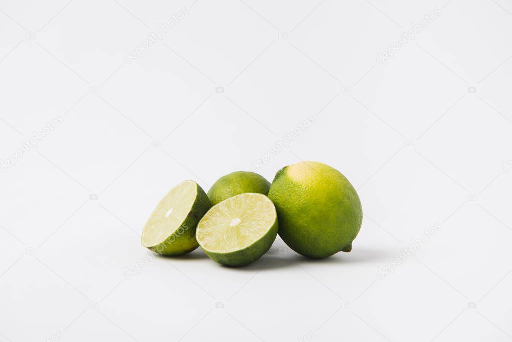 whole and halved limes laying on white background