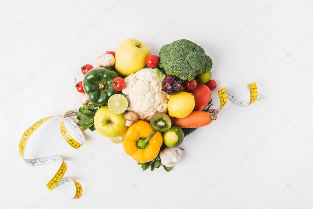 various vegetables laying on white background  with measuring tape