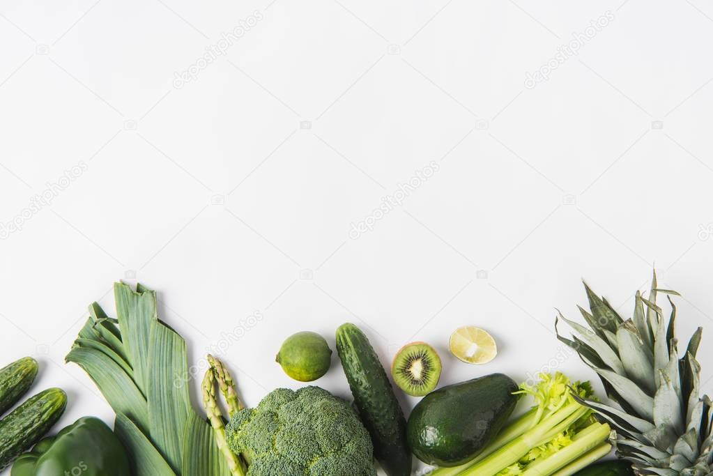 Border of green vegetables and fruits isolated on white background