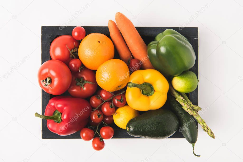 Top view of colorful vegetables and fruits in dark wooden box isolated on white background