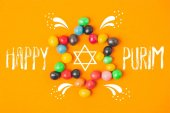 Photo top view of star made of sweets isolated on orange, purim holiday concept