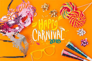 flat lay with lollipops and party objects isolated on orange, carnival concept
