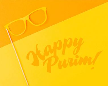 top view of masquerade mask on yellow and orange background, purim holiday concept