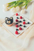 Photo close-up view of sweet tasty muffin in shape of bear, fresh raspberries and tulip flowers