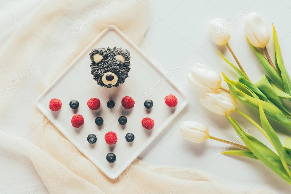 top view of sweet tasty muffin in shape of bear, fresh raspberries and tulip flowers