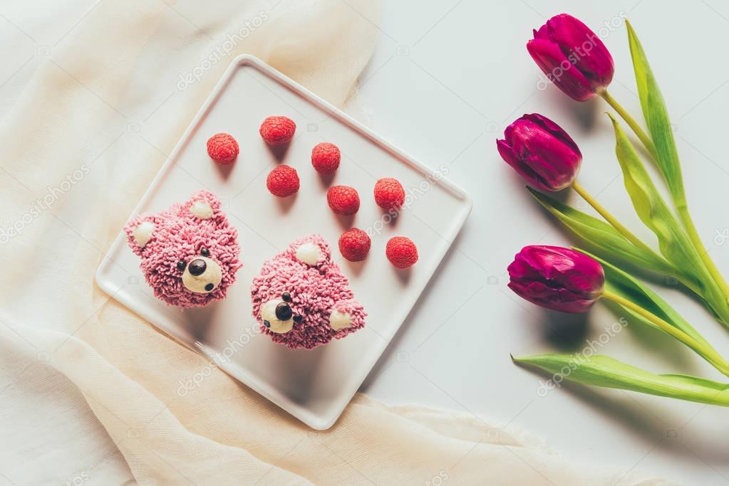 top view of sweet tasty muffins in shape of bears, fresh raspberries and tulip flowers