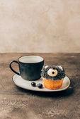 Fotografie süße leckere Blueberry Muffin in Form eines Bären und schwarze Becher auf Platte