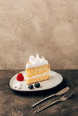 close-up view of sweet delicious cake with berries and whipped cream on plate