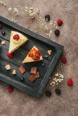 pohled shora na sladké chutné koláčky s čokoládou a ovocem na dřevěný tác