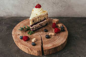 close-up view of sweet tasty cake with whipped cream and berries on wooden board