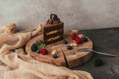 Photo close-up view of sweet tasty chocolate cake with berries on wooden board