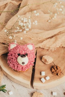top view of sweet pink muffin in shape of bear and nuts with sugar on wooden board