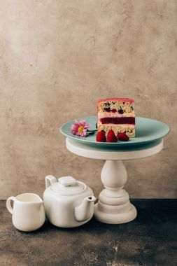 sweet tasty cake with raspberries and flower and kettle with porcelain jug