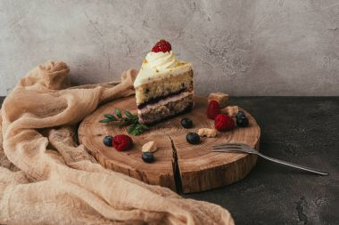 close-up view of delicious fruity cake with whipped cream on wooden board