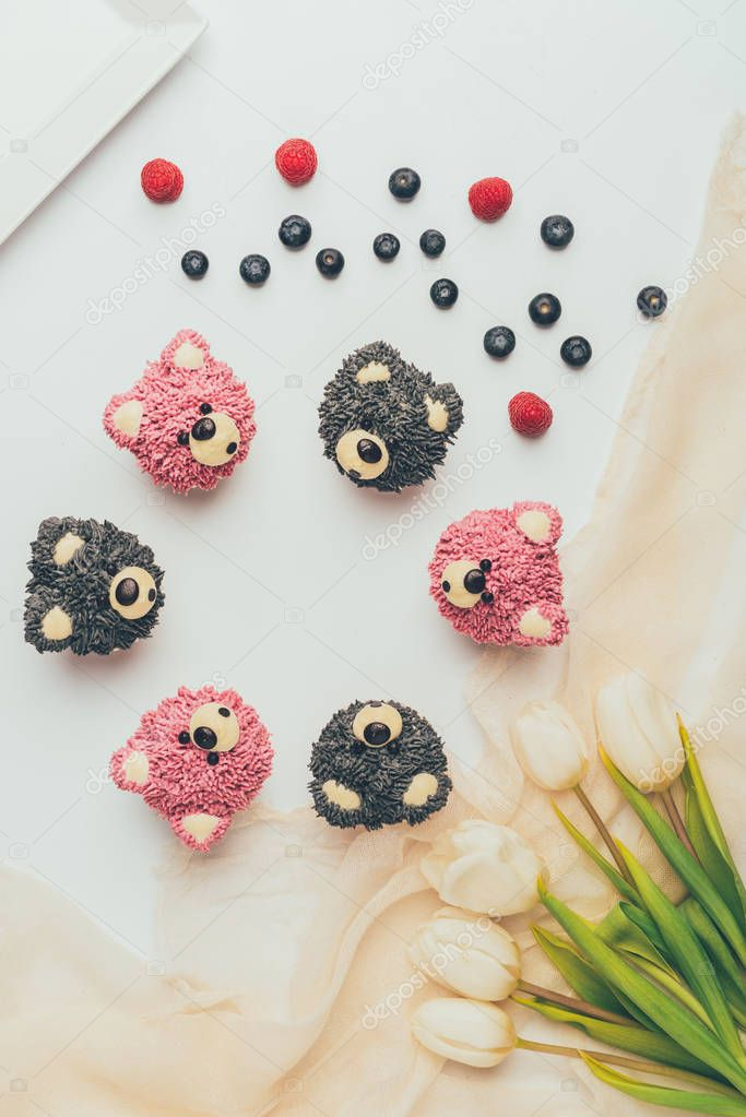 top view of delicious fruity muffins in shape of bears and beautiful tulips