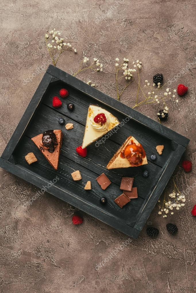top view of pieces of delicious cakes with chocolate and berries on wooden tray