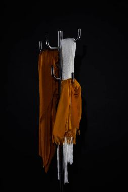 various scarves hanging on coat rack isolated on black