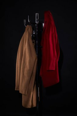 Classic coats on coat rack isolated on black stock vector