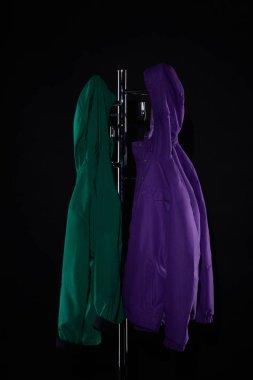 Raincoats hanging on coat rack isolated on black stock vector