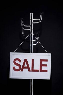 sale signboard hanging on coat rack isolated on black
