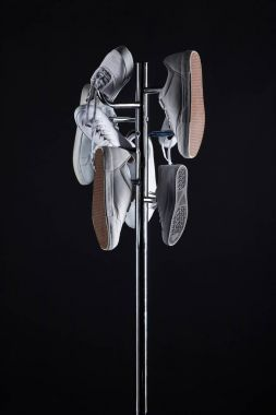 various shoes hanging on coat rack on black