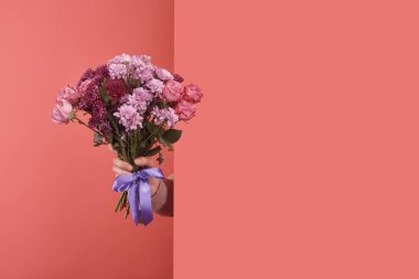 woman sticking out flowers bouquet behind wall on red