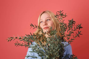 young woman with bunch of eucalyptus branches isolated on red