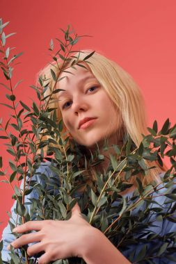 attractive young woman with bunch of eucalyptus branches isolated on red