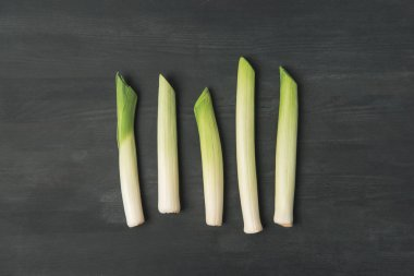 top view of arranged fresh leek on dark tabletop