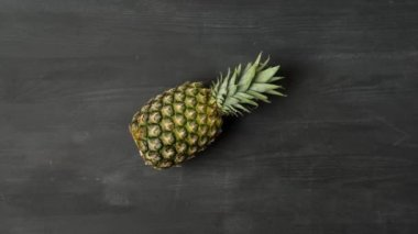 stop motion footage with fresh ripe pineapple rolling on dark tabletop