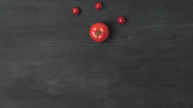 stop motion footage with fresh tomato and cherry tomatoes on dark grey surface
