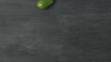 stop motion footage with avocados rolling on dark surface