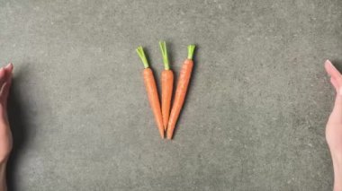stop motion footage with female hands and ripe carrots on grey concrete surface