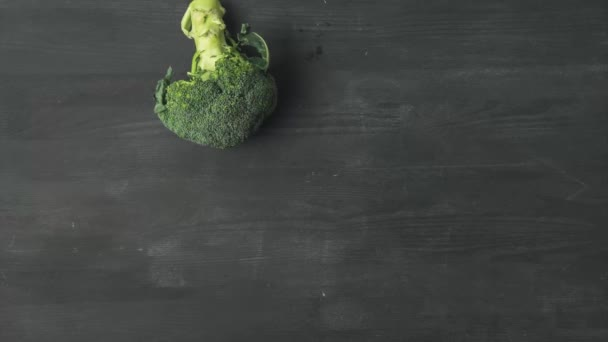stop motion footage with fresh broccoli rolling on dark surface