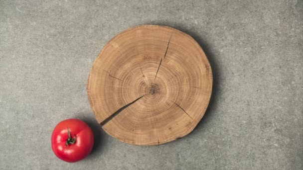 Stop motion footage of preparing tomato ketchup on wooden stump on grey concrete surface