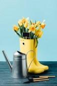 zblízka pohled žluté kytice květin a prázdné tabule v holínkách konev a zahrádkářských potřeb na dřevěný povrch na modré