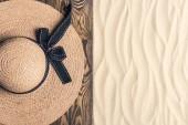 Slamák na dřevěném molu na písečné pláži