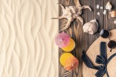 Cocktails and straw hat with seashells on light sand