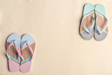 Colorful flip flops on sandy beach
