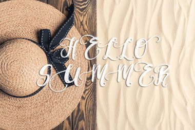 Straw hat on wooden pier on sandy beach with hello summer inscription