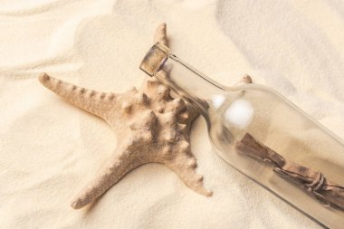 Starfish and bottle with letter on light sand