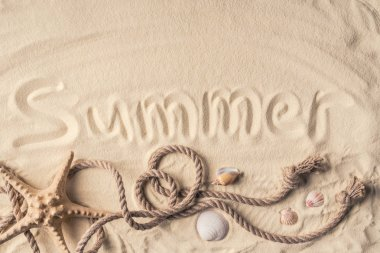 Starfish and shells with rope on light sand with summer inscription