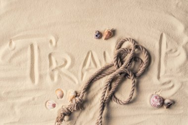 Rope and shells on sandy beach with rope and Travel inscription