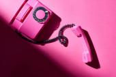 Top kilátás vintage rózsaszín telefon árnyékos fényes felületen