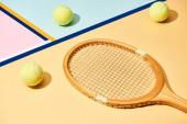Dřevěné tenisové rakety a míče na pozadí s modrými liniemi