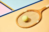 Žlutý tenisový míček na raketě na pozadí s modrými liniemi