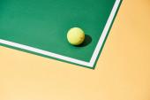 Tenisový míček se stínem na zeleném a žlutém povrchu s bílou čárou