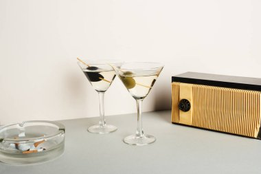 Martini cocktails with ashtray and cigarette butts and vintage radio on white background