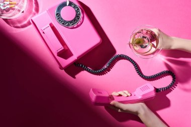 Cropped view of woman holding cocktail and telephone handset beside astray with cigarette butts on pink surface
