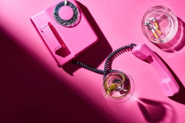 Top view of cocktail and retro telephone beside astray with cigarette butts on pink surface